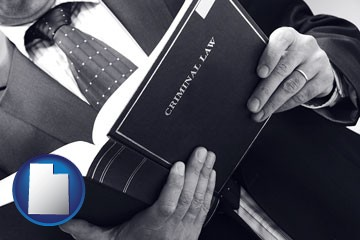 an attorney reading a criminal law book - with Utah icon